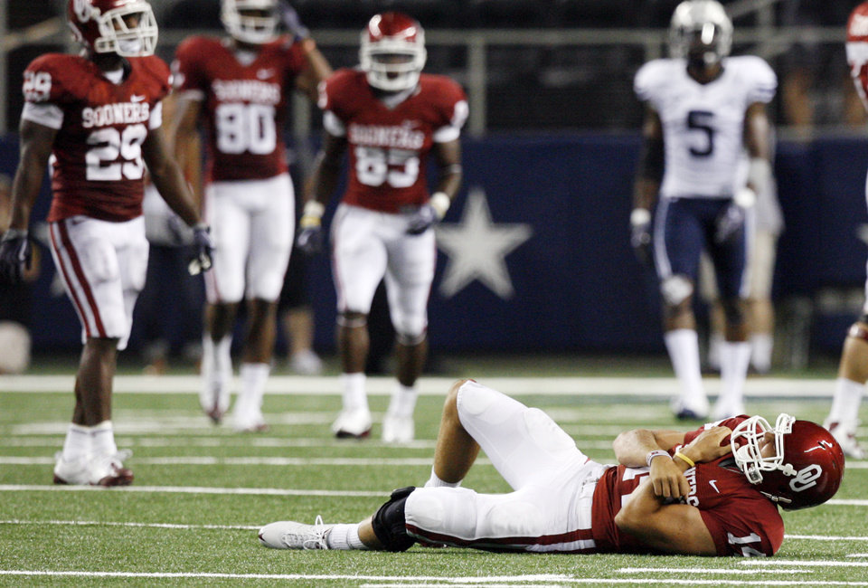 Photo - SHOULDER INJURY: OU quarterback Sam Bradford (14) lays on the turf after being injured late in the second quarter during the college football game between the Brigham Young University Cougars (BYU) and the University of Oklahoma Sooners (OU) at Cowboys Stadium in Arlington, Texas, Saturday, September 5, 2009. Bradford left the field after the play and did not return. BYU won, 14-13. By Nate Billings, The Oklahoman ORG XMIT: KOD