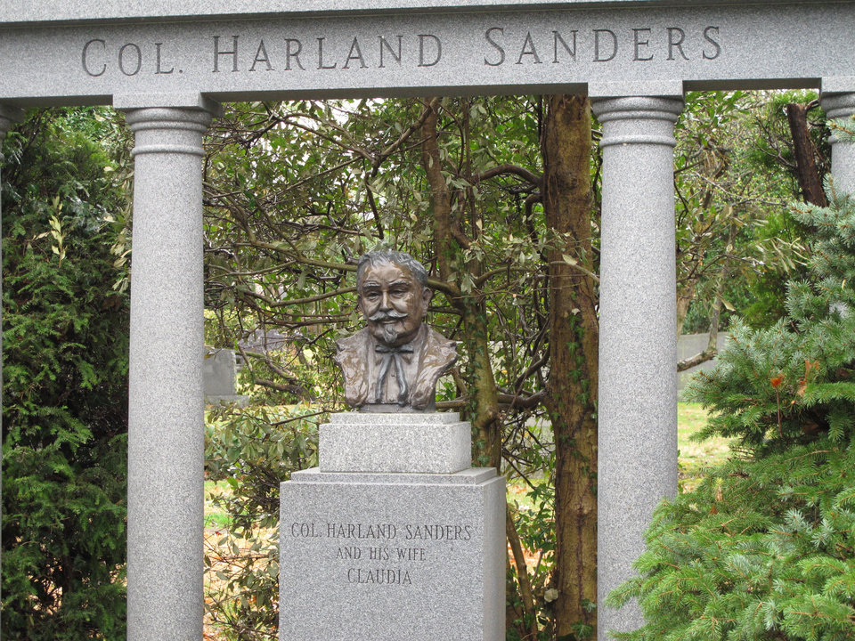 Photo - This April 3, 2014 photo shows a bust of Colonel Harland Sanders marking the KFC founder's grave at Cave Hill Cemetery in Louisville, Ky. The nearly 300-acre cemetery features ornate marble and granite monuments and is shaded by a wide variety of trees that loom over the rolling grounds. (AP Photo/Bruce Schreiner)