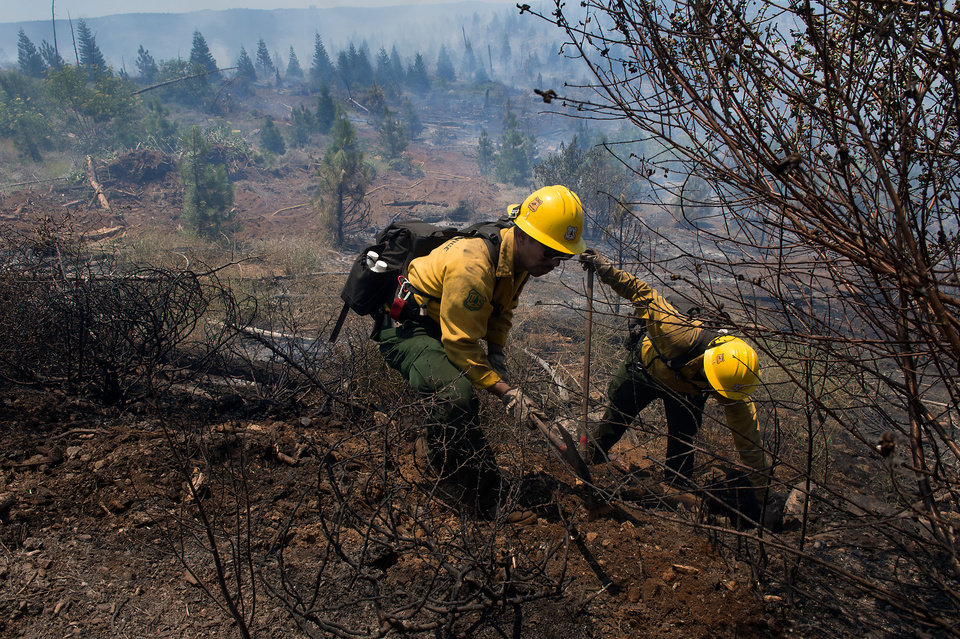 Photo - U.S. Forest Service fire crew members Madison Hampton, left, and Robert Keck, from Plumas National Forest, work north of Highway 50 near Kyburz, Calif. on Tuesday, July 9, 2013. More than 800 personnel are working a wildland blaze today near Kyburz that is 40 percent contained. Despite progress overnight, the fire burning near Kyburz in the Eldorado National Forest is still restricting travel through the Sierra on Highway 50.  (AP Photo/The Sacramento Bee, Randall Benton)  MAGS OUT; LOCAL TV OUT (KCRA3, KXTV10, KOVR13, KUVS19, KMAZ31, KTXL40); MANDATORY CREDIT