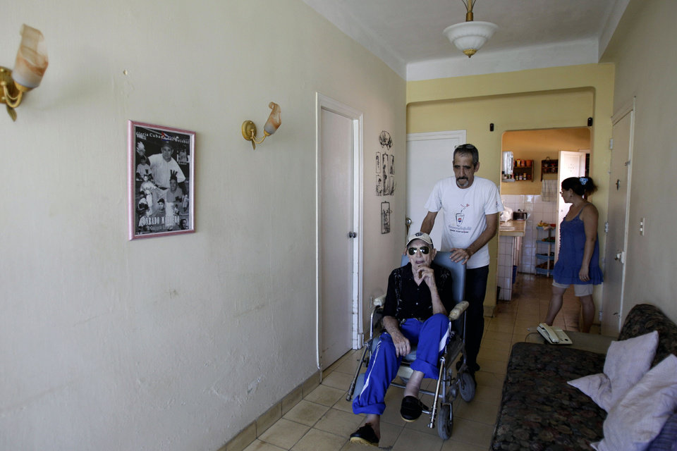 Photo - In this April 23, 2013 photo, Conrado Marrero, the world's oldest living former major league baseball player, is pushed in a wheelchair by his grandson Rogelio Marrero at their home two days before is 102nd birthday in Havana, Cuba. In addition to his longevity, the former Washington Senator has much to celebrate this year. After a long wait, he finally received a $20,000 payout from Major League baseball granted to old-timers who played between 1947 and 1979. The money had been held up since 2011 due to issues surrounding the 51-year-old U.S. embargo on Cuba, which prohibits most bank transfers to the Communist-run island. But the payout finally arrived in two parts, one at the end of last year, and the second a few months ago, according to Marrero's family. (AP Photo/Franklin Reyes)