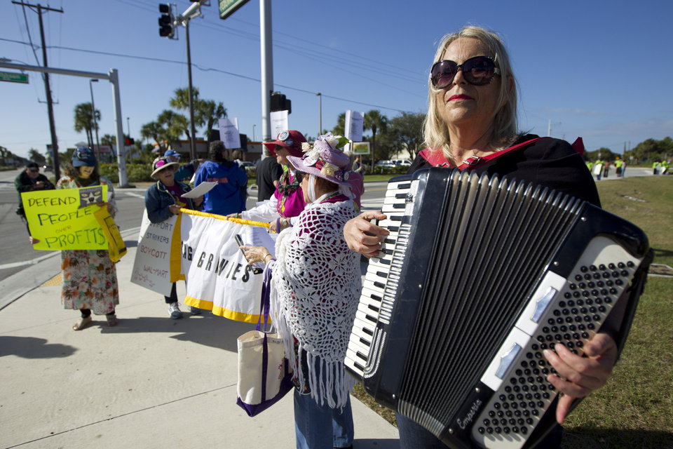 Photo -   Jackie Maye, plays her accordion during a protest against Wal-Mart in Boynton Beach, Fla., Friday, Nov 23, 2012. Wal-Mart employees and union supporters are taking part in today's nationwide demonstration for better pay and benefits A union-backed group called OUR Walmart, which includes former and current workers, was staging the demonstrations and walkouts at hundreds of stores on Black Friday, the day when retailers traditionally turn a profit for the year. (AP Photo/J Pat Carter)