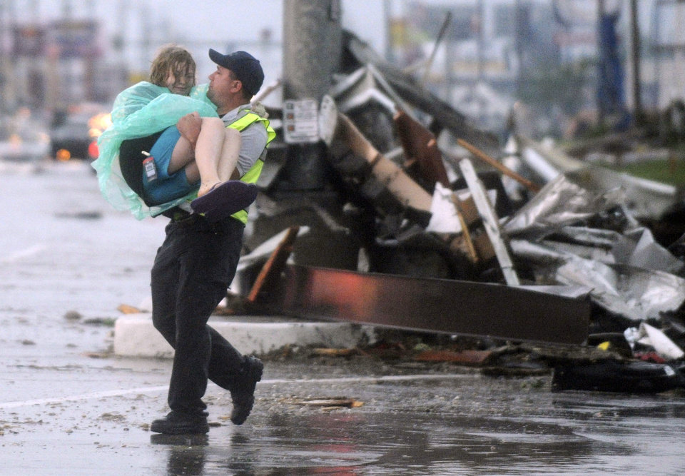 Photo - An emergency worker carries a girl to safety from the remains of Academy Sports  in Joplin, Mo. after a tornado struck the city on Sunday evening, May 22, 2011. (AP Photo/The Joplin Globe, Roger Nomer) ORG XMIT: MOJOP105