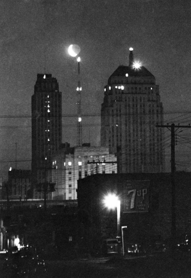 OKLAHOMA CITY / SKY LINE / OKLAHOMA:  At 4:30 A.M. a half moon, that seemed as larger as our largest building came floating over the Civic Center, The Radio Tower of the sheriff's office tried it's best to reach it.  The Apco Tower on left and the 1st national Bank on the right.  Staff photo by C. J. Kaho.  Photo taken 05/05/1948 and unpublished.  Photo arrived in library 05/20/1948.