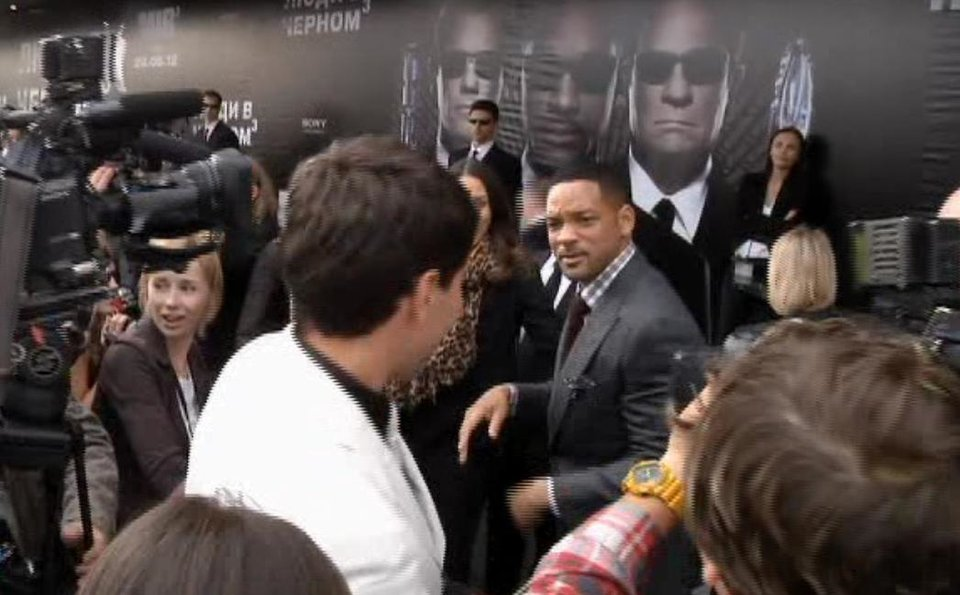 Photo -   In this video image taken from AP video U.S. actor Will Smith, center right, walks away from reporter Vitalii Sediuk, white suit, from the Ukrainian television channel 1+1 after slapping him on the red carpet before the premiere of