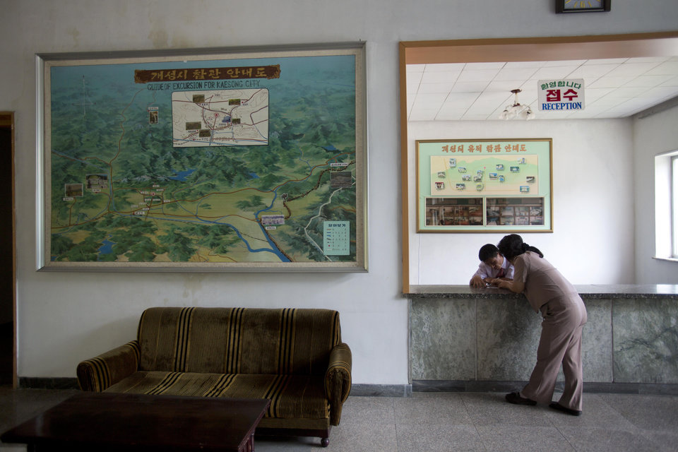 In this Sept. 11, 2012 photo, employees confer at the reception desk of a hotel for foreign tourists in Kaesong, North Korea. (AP Photo/David Guttenfelder)