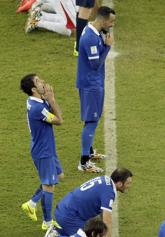 Photo - Greece's Giorgos Karagounis, left, and his teammates wait in the center circle during the penalty shoot-out of the World Cup round of 16 soccer match between Costa Rica and Greece at the Arena Pernambuco in Recife, Brazil, Sunday, June 29, 2014. Costa Rica won 5-3 on penalties and advanced to the quarterfinal.  (AP Photo/Hassan Ammar)