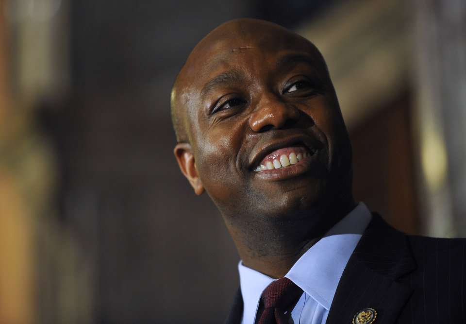 Photo - U.S. Rep. Tim Scott smiles during a press conference announcing him as Jim DeMint's replacement in the U.S. Senate at the South Carolina Statehouse on Monday, Dec. 17, 2012, in Columbia, S.C. South Carolina Gov. Nikki Haley announced Scott, as Sen. Jim DeMint's replacement, making him the only black Republican in Congress and the South's first black Republican senator since Reconstruction. (AP Photo/Rainier Ehrhardt)
