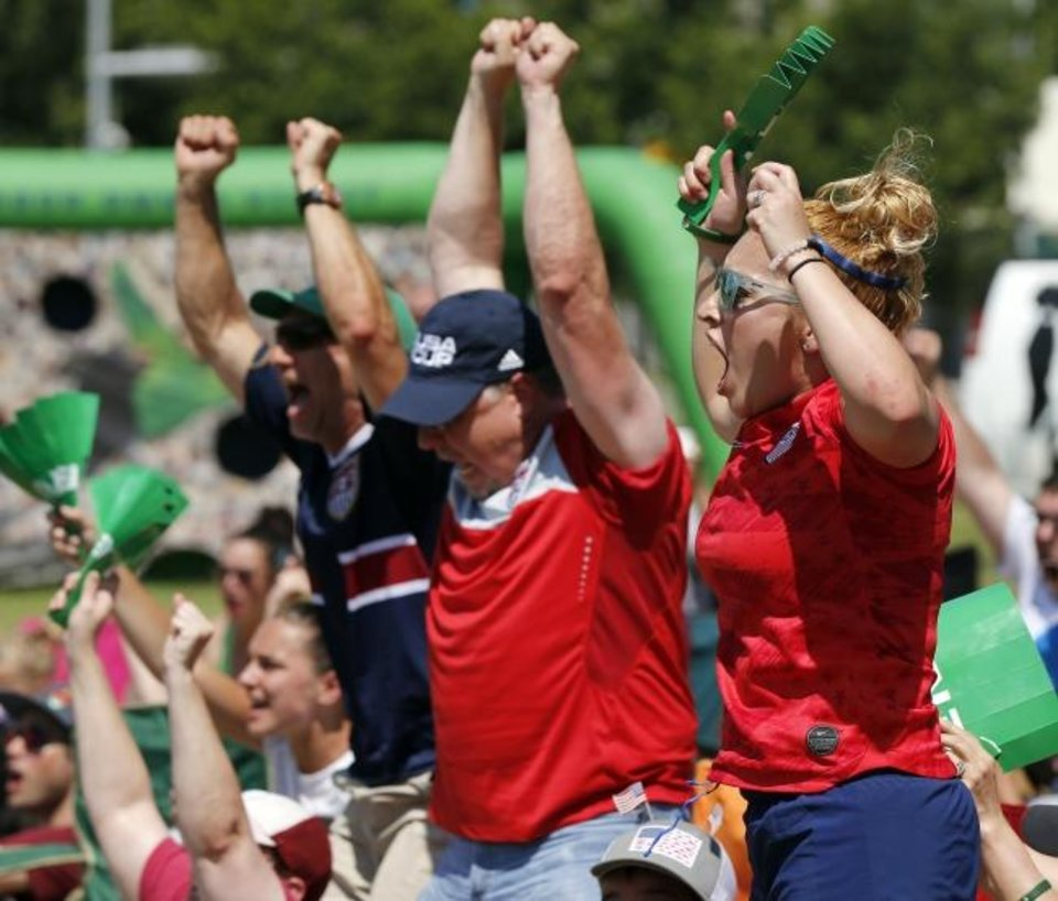 Photo -  Stephanie Torrez, right, cheers with other fans Sunday after a U.S. goal in the 69th minute during a World Cup watch party at Together Park dowtown, hosted by the OKC Energy FC. [Nate Billings/The Oklahoman]