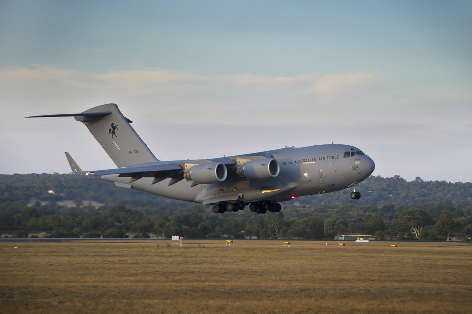 Photo - In this Friday, March 28, 2014 photo released by the Australian Defence, a Royal Australian Air Force C-17 Globemaster prepares to land at RAAF Pearce Base to help with the search for the missing Malaysia Airlines Flight 370, in Perth, Australia. Objects spotted floating in a new search area for debris from the missing Malaysian jetliner need to be recovered and inspected before they can be linked to the plane, Australian officials said Saturday. Eight planes were ready to comb the newly targeted area off the west coast of Australia after several objects were spotted Friday, including two rectangular items that were blue and gray, and ships on the scene will attempt to recover them, the Australian Maritime Safety Authority said. (AP Photo/Australian Defence, Oliver Carter)