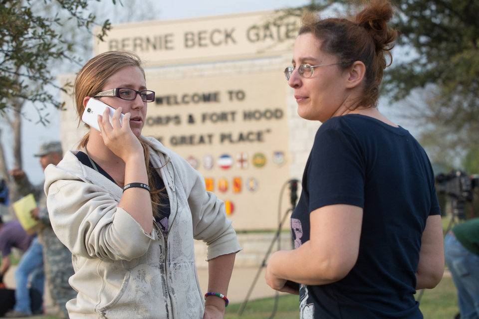 Photo - Krystina Cassidy and Dianna Simpson attempt to make contact with their husbands who are stationed inside Fort Hood, while standing outside of the Bernie Beck Gate, on Wednesday, April 2, 2014, in Fort Hood, Texas. At least one person was killed and 14 injured in a shooting Wednesday at Fort Hood, and officials at the base said the shooter is believed to be dead. (AP Photo/ Tamir Kalifa)
