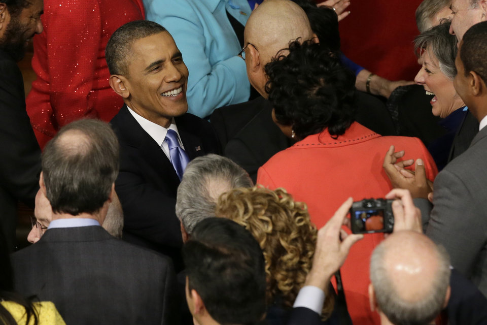 Photo - President Barack Obama is greeted as he arrives to give his State of the Union address on Capitol Hill in Washington, Tuesday Jan. 28, 2014. (AP Photo/J. Scott Applewhite)