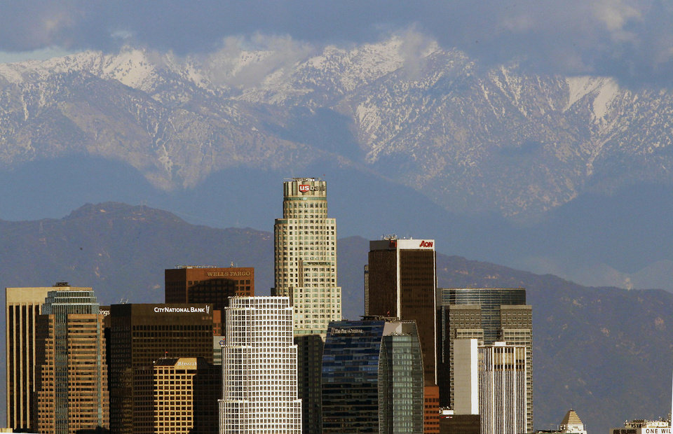 The snow covered San Gabriel Mountains rise behind the downtown Los Angeles downtown skyline Thursday, Dec 27, 2012. (AP Photo/Nick Ut)
