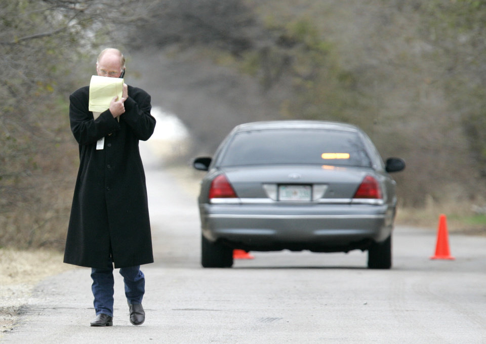 Photo - Bethany Police Chief Neal Troutman looks at notes and talks on his cell phone near Stinchcomb Avenue and NW 50th street where the search for  missing pregnant woman Lauren Barnes is underway in Oklahoma City, Okla. Nov. 29, 2007.  BY STEVE GOOCH, THE OKLAHOMA.  ORG XMIT: KOD