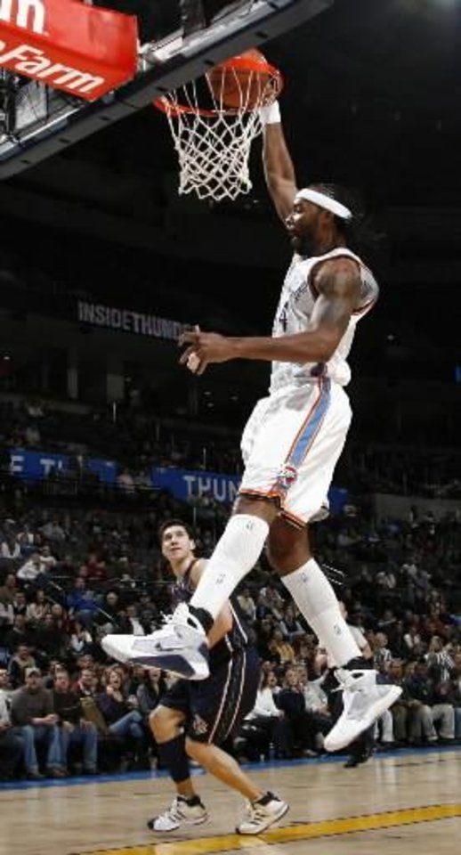 Photo - Oklahoma City's  Chris  Wilcox dunks the ball as Eduardo Najera of New Jersey watches in the first half during the NBA basketball game between the Oklahoma City Thunder and the New Jersey Nets at the Ford Center in Oklahoma City, Monday, January 26, 2009. BY NATE BILLINGS