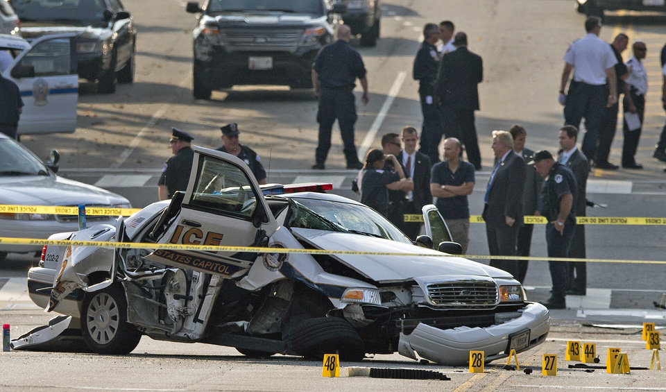 Photo - A damaged Capitol Hill police car is surrounded by crime scene tape after a car chase and shooting in Washington, Thursday, Oct. 3, 2013. On Thursday, police shot and killed 34-year-old Miriam Carey, of Stamford, Conn., after a car chase that began when Carey tried to breach a barrier at the White House. (AP Photo/ Evan Vucci)