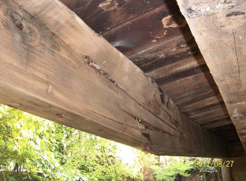 Photo - Cracked wooden girders made the one-lane bridge east of Washington, OK, structurally deficient and unsafe for vehicles carrying large loads.   Photo Provided - PHOTO PROVIDED