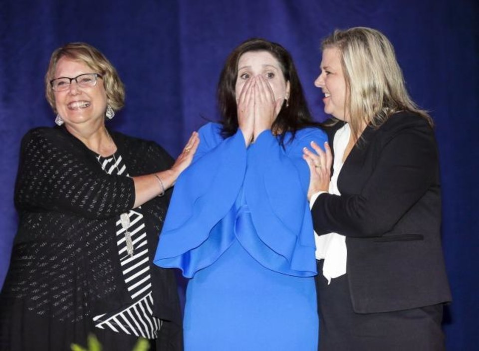 Photo -  Jena Nelson, a Deer Creek Middle School teacher, center, reacts between finalists Patricia Lightfoot, a Weatherford Middle School teacher, left, and Michelle Rahn, a Will Rogers Junior High teacher, as Nelson is announced the 2020 Oklahoma Teacher of the Year at State Fair Park on Tuesday. [Nate Billings/The Oklahoman]
