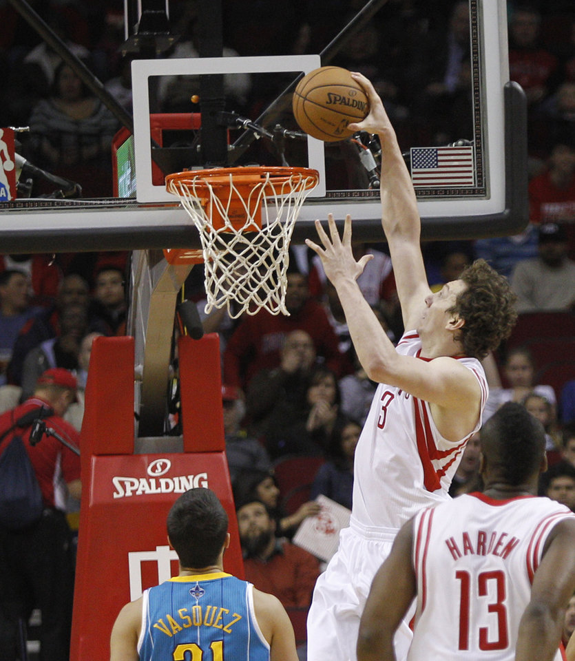 Photo - Houston Rockets center Omer Asik (3) dunks over New Orleans Hornets point guard Greivis Vasquez (21) during the first half of an NBA basketball game on Wednesday, Jan. 2, 2013, in Houston. (AP Photo/Bob Levey)
