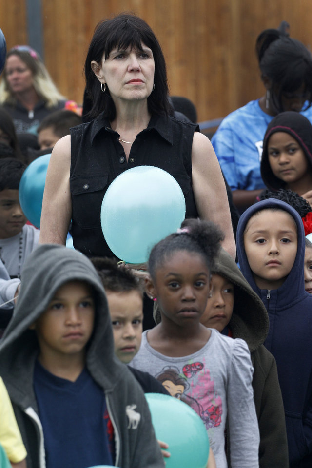 Photo - Eugene Field Elementary School kindergarten teacher Vicky Watson and her class wait to release balloons during a memorial for her student Evelyn De Los Santos, in Oklahoma City, Friday, May  11,  2012. Evelyn was murdered by her father in March 2012. Photo By Steve Gooch, The Oklahoman