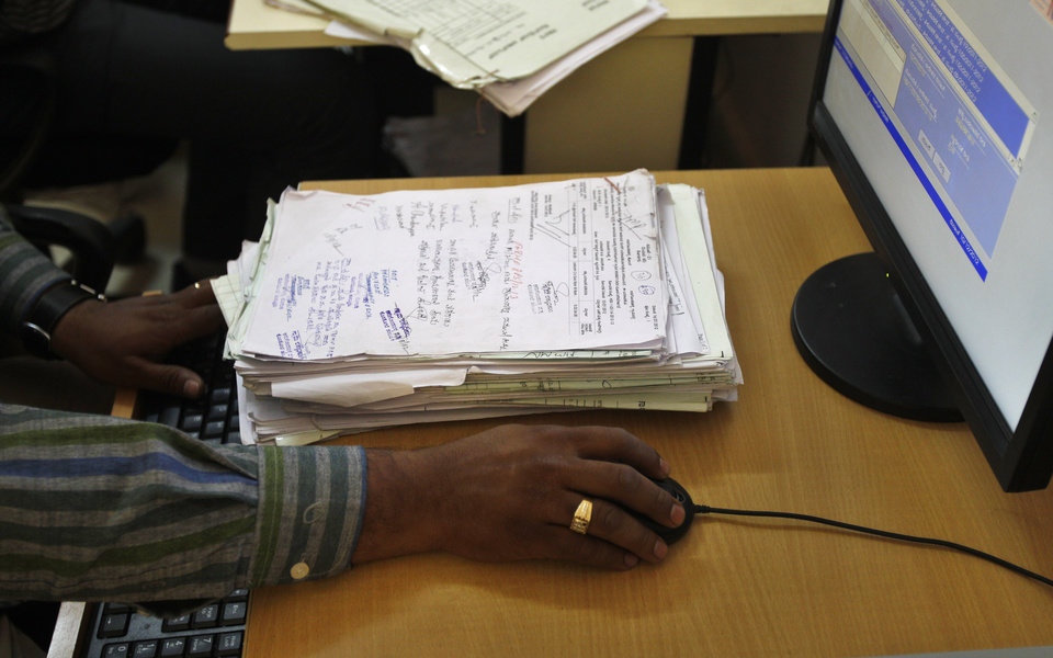 Photo - In this Dec. 10, 2012 photo, a government official enter authorized land records in a computer at the government registrar's office in Hoskote 30 Kilometers (19 miles) from Bangalore in the southern Indian state of Karnataka. For years, Karnataka's land records were a quagmire of disputed, forged documents maintained by thousands of tyrannical bureaucrats who demanded bribes to do their jobs. In 2002, there were hopes that this was about to change. (AP Photo/Aijaz Rahi)