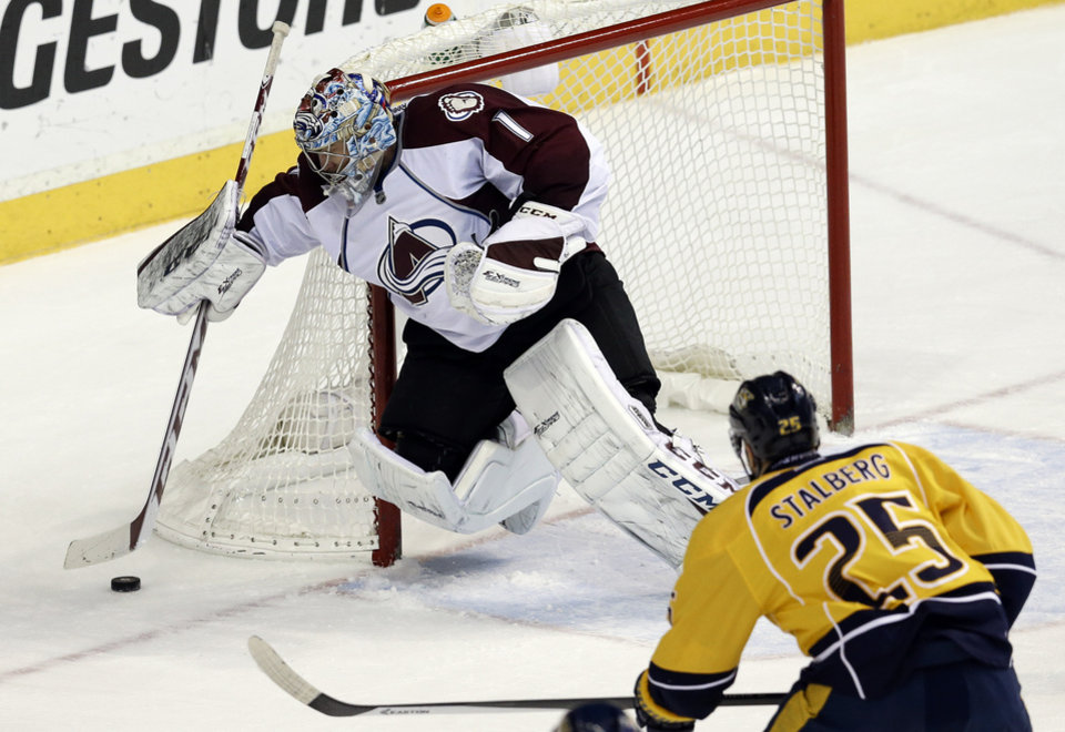 Photo - Colorado Avalanche goalie Semyon Varlamov (1), of Russia, covers up the puck as Nashville Predators forward Viktor Stalberg (25), of Sweden, closes in during the second period of an NHL hockey game, Saturday, Jan. 18, 2014, in Nashville, Tenn. (AP Photo/Mark Humphrey)