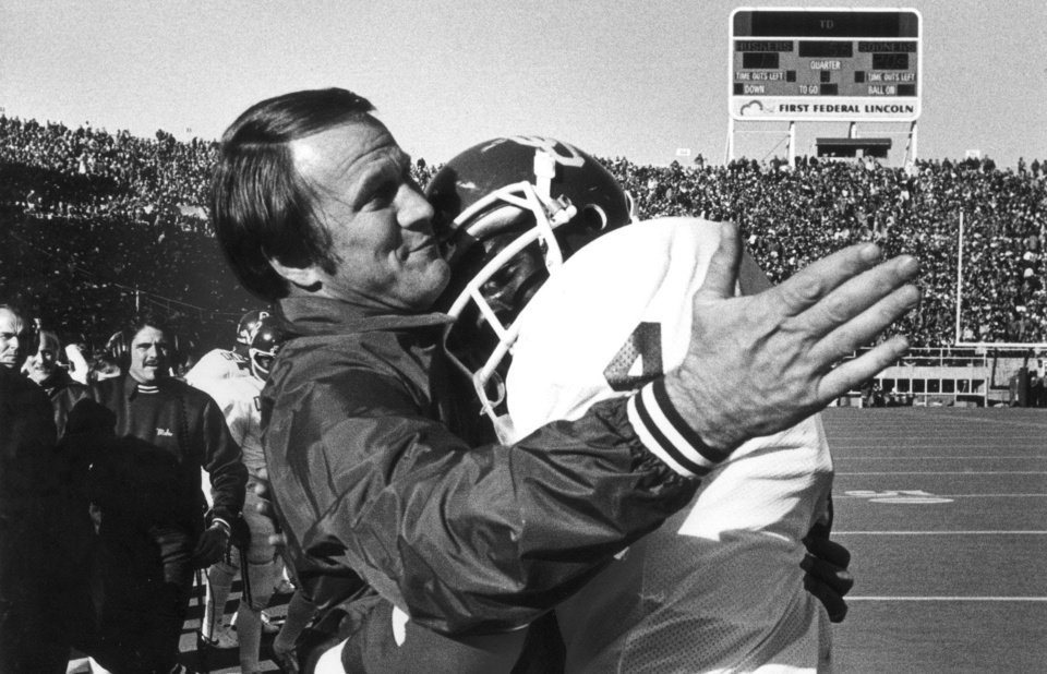 Photo - OU college football coach Barry Switzer hugs Buster Rhymes, whose winning touchdown run put the lock on the University of Oklahoma's 21-17 victory over Nebraska in 1980.