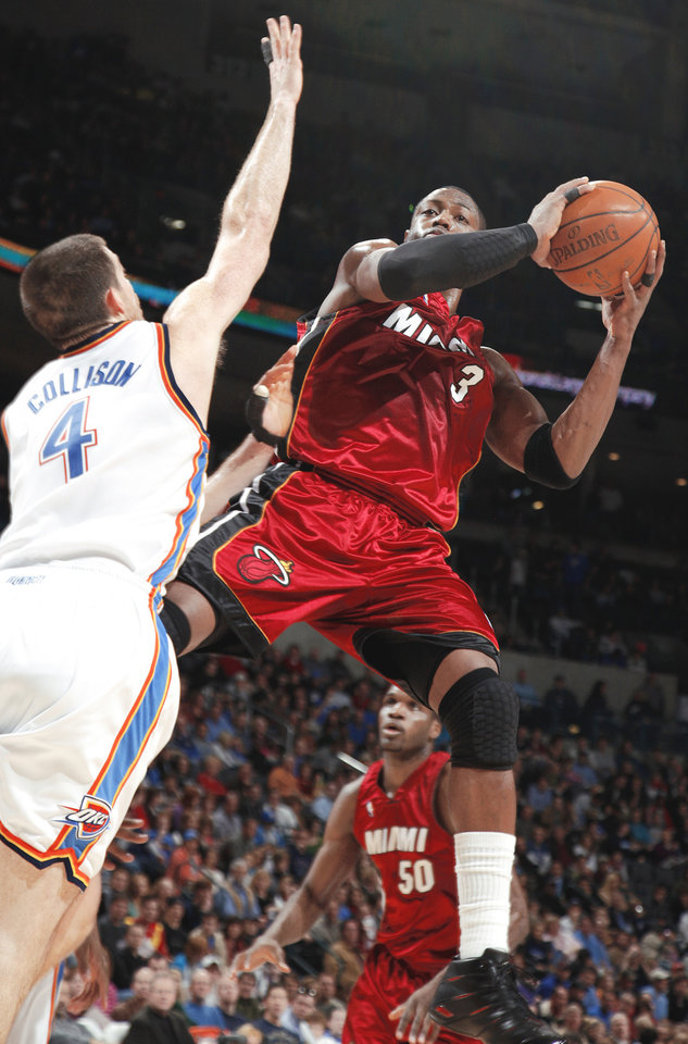 Photo - Miami's Dwyane Wade passes the ball during Sunday's game against the  Thunder. Wade scored 32 points on 14-of-28 shooting and had 10 assists.  PHOTO BY SARAH PHIPPS, THE OKLAHOMAN