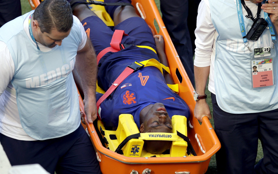 Photo - Netherlands' Bruno Martins Indi is carried off the pitch after a tackle during the group B World Cup soccer match between Australia and the Netherlands at the Estadio Beira-Rio in Porto Alegre, Brazil, Wednesday, June 18, 2014. (AP Photo/Michael Sohn)