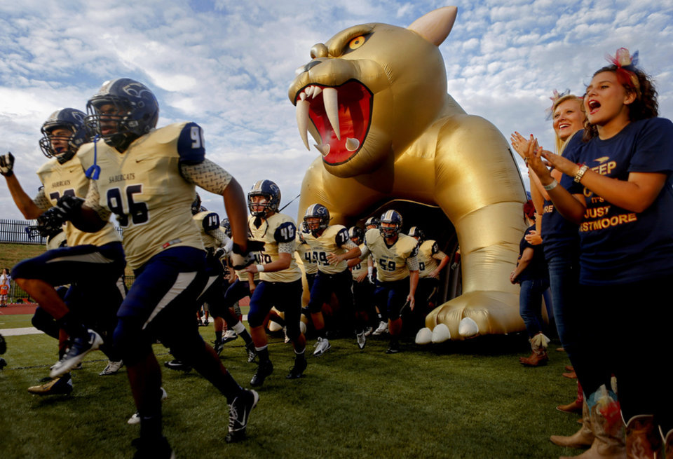Photo - The Southmoore team takes the field to play Westmoore before their high school football game in Moore, Okla., Friday, Sept. 13, 2013. Photo by Bryan Terry, The Oklahoman