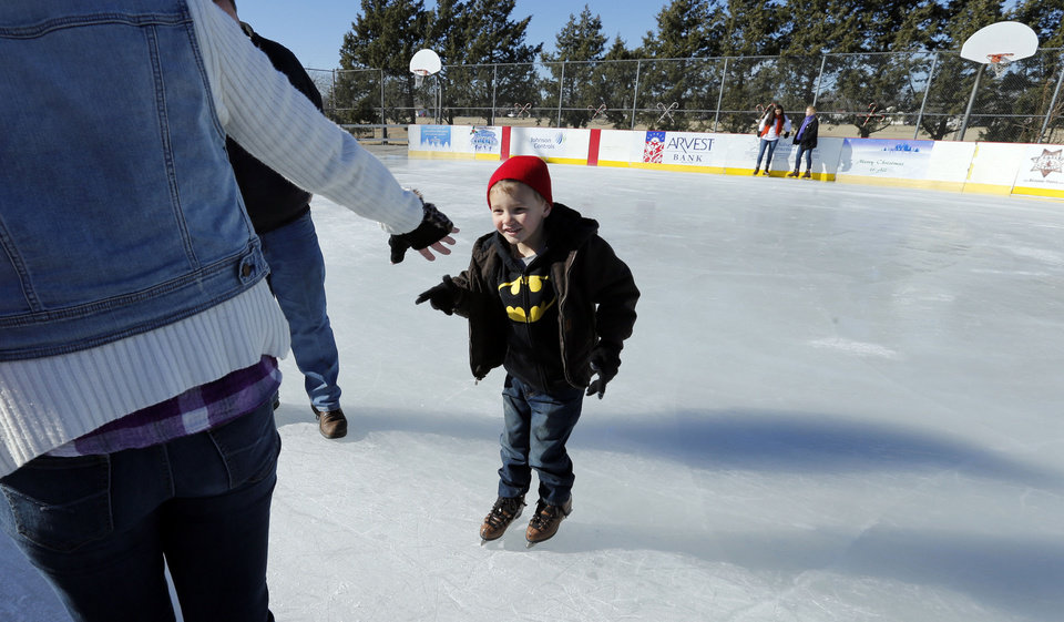 Photo - Weston Setzer, 5, reaches for a helping hand from his grandmother Rhonda Zimmer at the outdoor ice rink at Andrews Park in Norman. PHOTO BY STEVE SISNEY, THE OKLAHOMAN  STEVE SISNEY