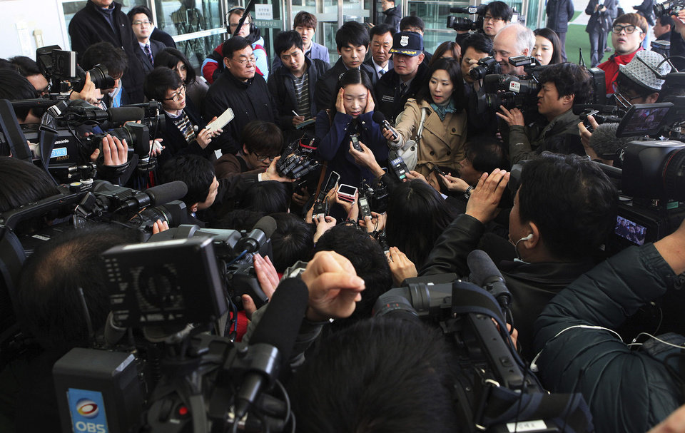 Photo - South Korean worker Kown Suk-mi who was working for a South Korean business in the North Korean city of Kaesong, top center, is surrounded by the media after returning from Kaesong at the customs, immigration and quarantine office in Paju, South Korea, near the border village of Panmunjom, Thursday, April 4, 2013.North Korea on Wednesday barred South Korean workers from entering a jointly run factory park just over the heavily armed border in the North, officials in Seoul said, a day after Pyongyang announced it would restart its long-shuttered plutonium reactor and increase production of nuclear weapons material.(AP Photo/Ahn Young-joon)