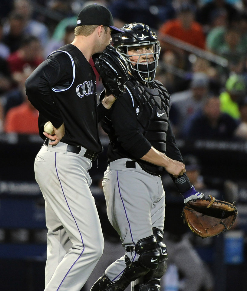 Photo - Colorado Rockies starting pitcher Jordan Lyles, left, and catcher Jordan Pacheco talk near the mound with two Atlanta Braves runners in scoring position during the third inning of a baseball game Friday, May 23, 2014, in Atlanta. (AP Photo/David Tulis)