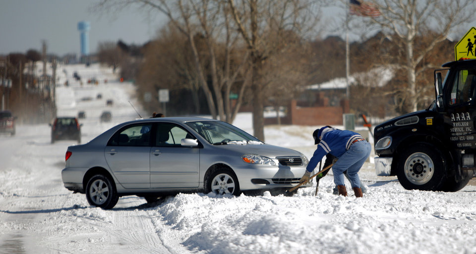 Photo - People try to dig out a car stuck in snow on NW 150th in Oklahoma City Wednesday, Feb. 2, 2011.  Photo by Sarah Phipps, The Oklahoman