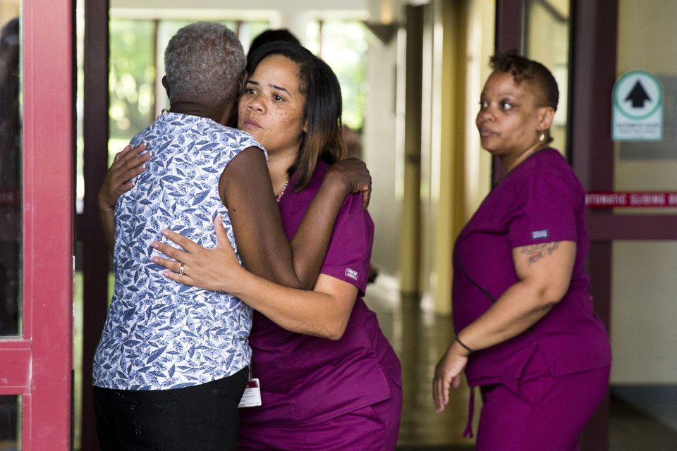 Photo - A hospital worker embraces a woman near the scene of a shooting at the Mercy Fitzgerald Hospital in Darby, Pa. on Thursday, July 24, 2014. A prosecutor said a gunman opened fire inside the psychiatric unit leaving one hospital employee dead and a second injured before being critically wounded himself. (AP Photo)