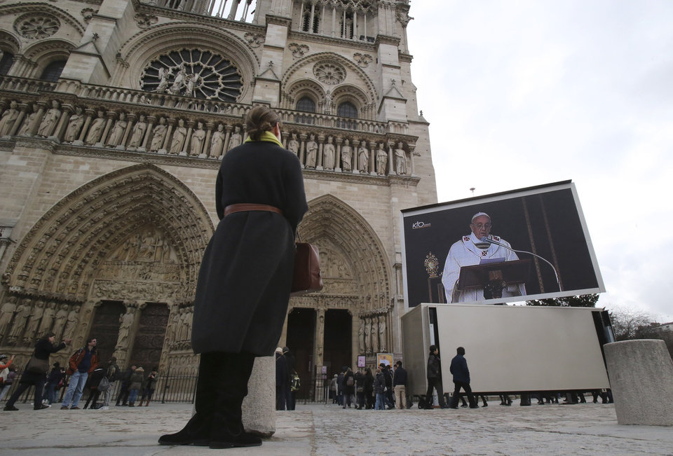 Photo - A woman watches the inauguration of Pope Francis on a giant screen outside Notre Dame cathedral, Paris, Tuesday, March 19, 2013. Pope Francis urged princes, presidents, sheiks and thousands of ordinary people gathered for his installation Mass on Tuesday to protect the environment, the weakest and the poorest, mapping out a clear focus of his priorities as leader of the world's 1.2 billion Catholics. (AP Photo/Michel Euler)