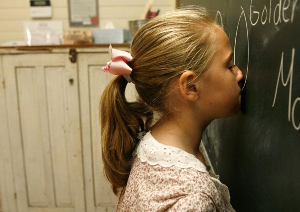Photo -  Jacquelyn Renner, 9, places her nose against the chalkboard to experience older forms of student discipline during 1889 School Camp at the 1889 Territory School in Edmond, Okla. Tuesday, July 7, 2009.  Photo by Ashley McKee, The Oklahoman   ORG XMIT: KOD