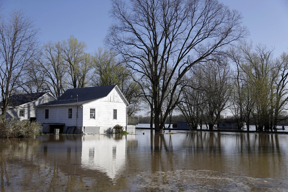 Houses are surrounded by floodwater from the Mississippi River Saturday, April 20, 2013, in Clarksville, Mo. Communities along the Mississippi River and other rain-engorged waterways are waging feverish bids to hold back floodwaters that may soon approach record levels. (AP Photo/Jeff Roberson)