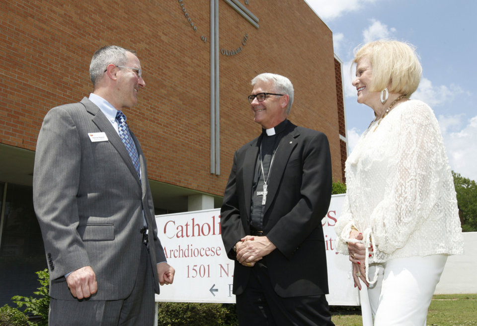 Photo -  Patrick Raglow, left, executive director of Catholic Charities, Oklahoma City Archbishop Paul S. Coakley, and Crossbeam campaign co-chairman Judy Love visit in front of the current Catholic Charities home. Photo by Paul Hellstern, The Oklahoman   PAUL HELLSTERN -