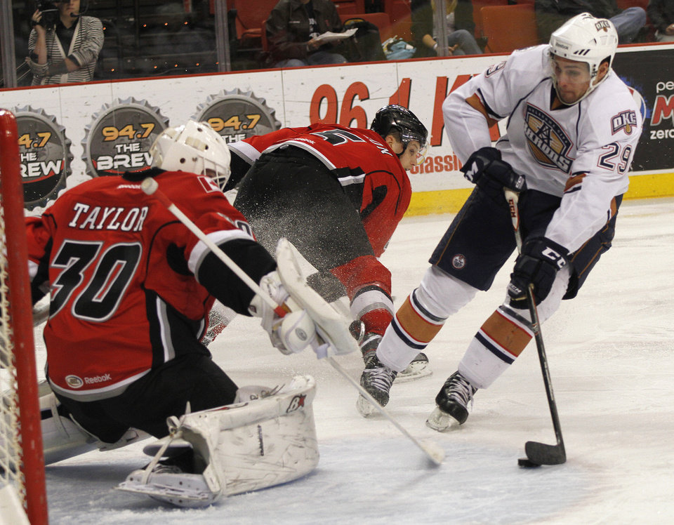 OKC's Chris VandeVelde (29) shoots a puck past Abbotsford goalie, Danny Taylor (3), during a game between the Oklahoma City Barons and the Abbotsford Heat in Oklahoma City, Sunday, Jan. 15, 2012.  Photo by Garett Fisbeck, For The Oklahoman
