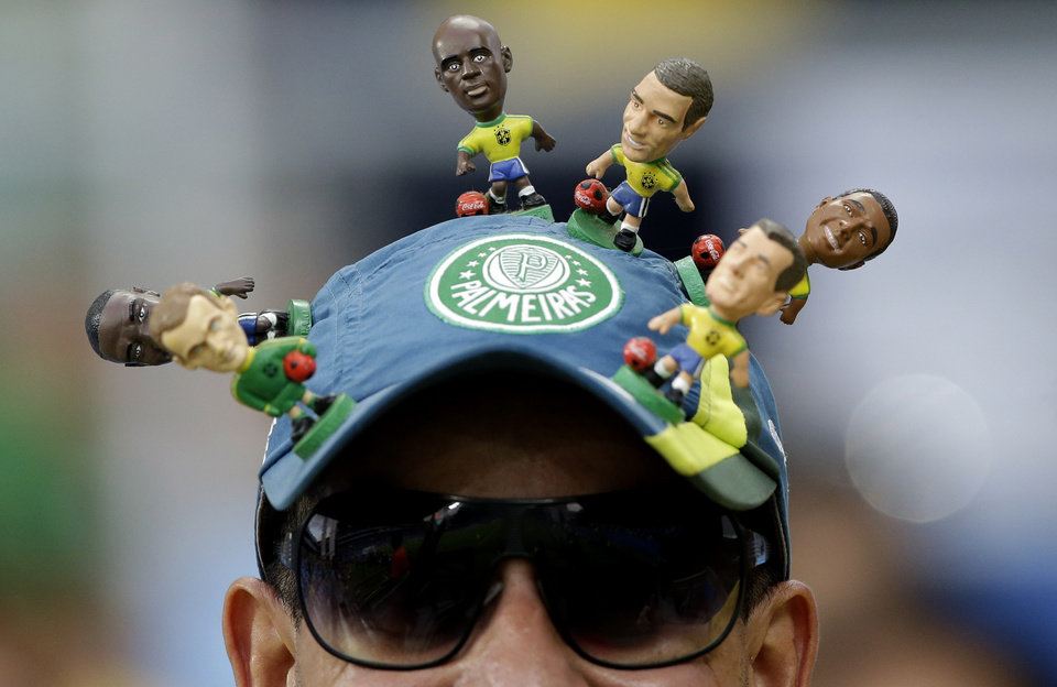 Photo - A spectator sports a footballing motif on his baseball cap ahead of the group H World Cup soccer match between Russia and South Korea at the Arena Pantanal in Cuiaba, Brazil, Tuesday, June 17, 2014.  (AP Photo/Lee Jin-man)