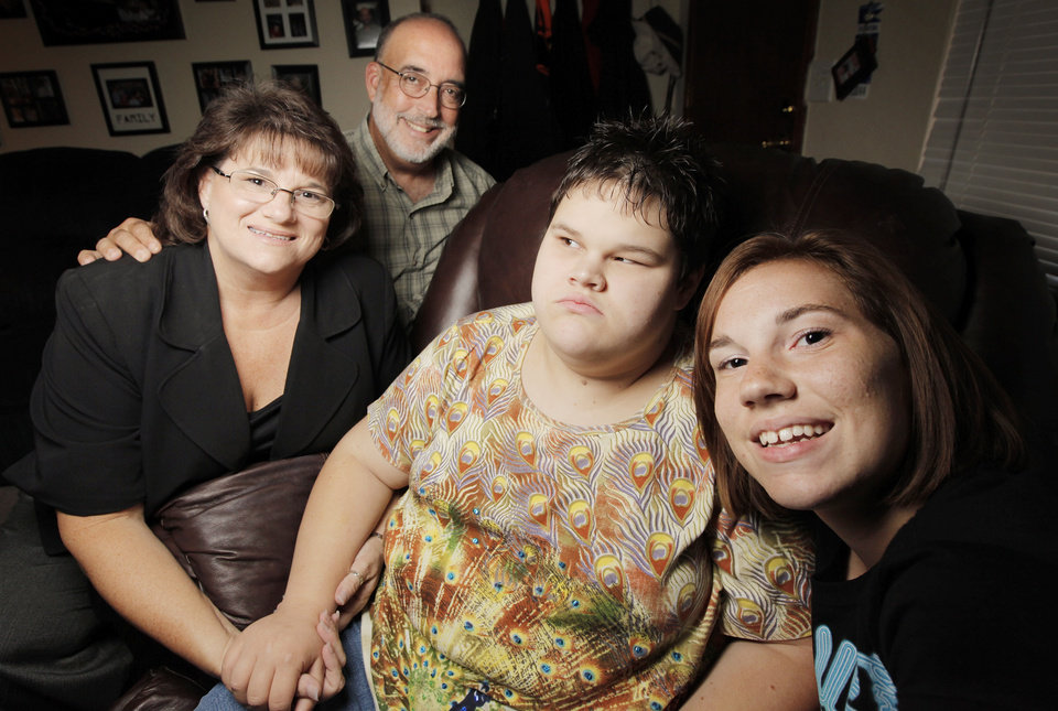 Photo - DEPARTMENT OF HUMAN SERVICES / DISABILITIES / ASSISTANCE: From left, Wanda Felty, her husband Rick Felty, and daughters Kayla White, 21, and Kerrie White, 16, pose for a photo at their home in Norman, Okla., Thursday, August 26, 2010. Wanda Felty was on a waiting list for five years before she received state funds from DHS to help with in-home support of her disabled daughter Kayla White. Wanda Felty is working to help the families who are still on the waiting list for aid. Photo by Nate Billings, The Oklahoman ORG XMIT: KOD