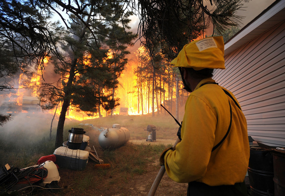Photo -   Firefighters from the Dean Creek Fire Department work to save a home south of Roundup, Mont. on June 26, 2012. Hundreds of families were forced from their homes south of Roundup as a fire pushed by strong winds burned more than 18,000 acres. (AP Photo/The Billings Gazette, Larry Mayer)