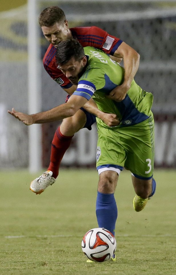 Photo - Chivas USA defender Tony Lochhead, top, Seattle Sounders midfielder Brad Evans for the ball during the first half of an MLS soccer match Wednesday, Sept. 3, 2014, in Carson, Calif. (AP Photo/Chris Carlson)