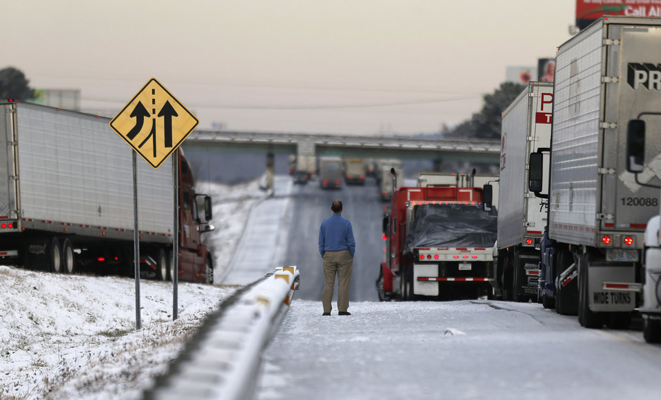 Photo - A man stands on the frozen roadway as he waits for traffic to clear along Interstate 75 Wednesday, Jan. 29, 2014, in Macon, Ga. A winter storm dumped snow and covered parts of the state with ice.  Gov. Nathan Deal said early Wednesday that the National Guard was sending military Humvees onto Atlanta's snarled freeway system in an attempt to move stranded school buses and get food and water to people. (AP Photo/John Bazemore)