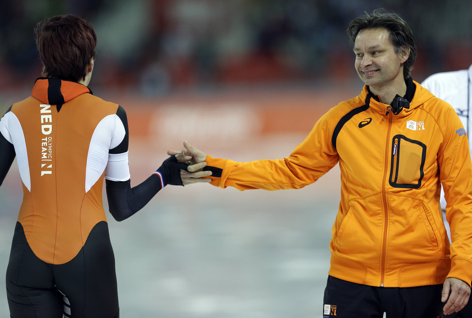 Photo - Gold medallist Jorien ter Mors of the Netherlands is congratulated by her coach Jeroen Otter, right, after she competed in the women's 1,500-meter speedskating race at the Adler Arena Skating Center at the 2014 Winter Olympics, Sunday, Feb. 16, 2014, in Sochi, Russia. (AP Photo/Patrick Semansky)