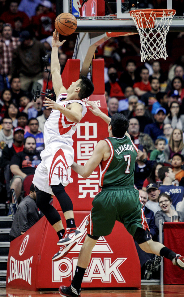 Photo - Houston Rockets guard Jeremy Lin (7) drives to the basket against Milwaukee Bucks forward Ersan Ilyasova (7) during the first half of an NBA basketball game, Wednesday, Feb. 27, 2013 in Houston. (AP Photo/Bob Levey)
