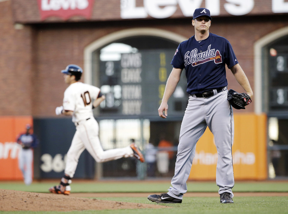 Photo - San Francisco Giants' Tyler Colvin, left, round the bases after his solo home run off Atlanta Braves starting pitcher Gavin Floyd during the second inning of a baseball game on Monday, May 12, 2014, in San Francisco. (AP Photo/Marcio Jose Sanchez)
