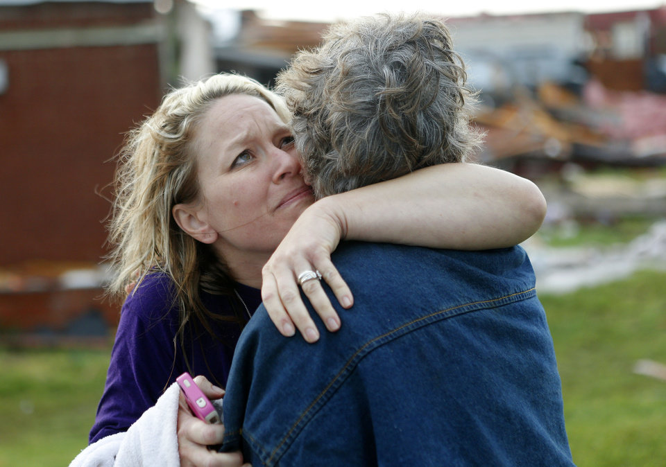 Photo - Eryn Ohl hugs her grandmother, Jerry Dirks, after both of their homes were hit by a tornado just south of Carney Okla., on Sunday, May 19, 2013. Five people took shelter in the cellar of the home when the tornado struck. Photo by Bryan Terry, The Oklahoman