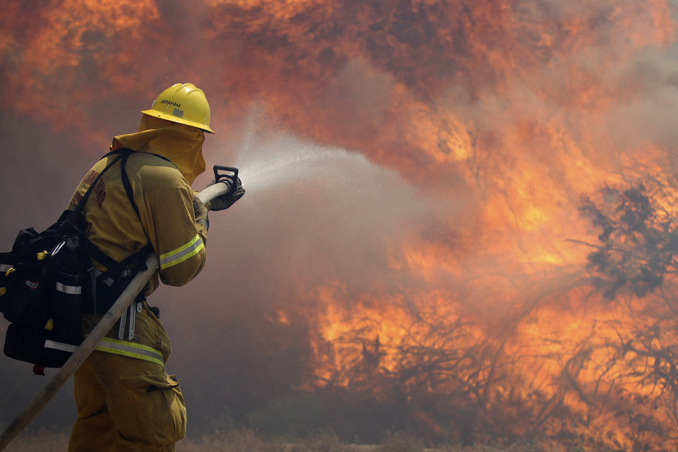 Photo -   Firefighter Scott Abraham, of the San Bernardino County Fire Department, sprays water as his crew tries to keep the fire from crossing a San Diego County road Friday, May 25, 2012, near Julian, Calif. The blaze broke out Thursday afternoon east of Julian near Banner Grade. About 100 homes were temporarily evacuated in the Shelter Valley area along Highway 78 during the early stages of the fire but that order was lifted late Thursday. (AP Photo/Gregory Bull)