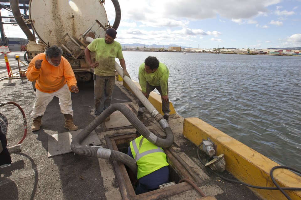 Photo - Workers from Pacific Environmental Corporation pumped out a broken Matson pipeline located under the neighboring Horizon shipyard dock in Honolulu Hawaii on Wednesday Sept. 11, 2013. An estimated 233,000 gallons of molasses spilled into the water on Monday.  (AP Photo/Honolulu Star-Advertiser, Cindy Ellen Russell)